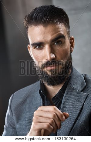 Portrait of confident young businessman with beard.