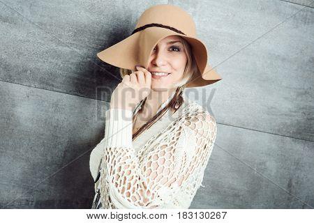 Stylish playful woman wearing hat, smiling.