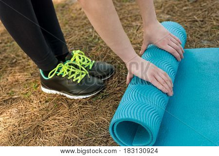 Girl in sports shoes spreads blue karemat for yoga warm-up or meditation