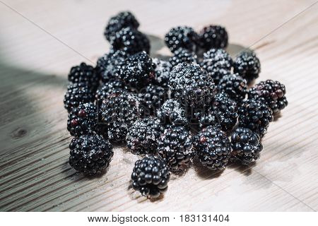 Ripe berries of dewberry on a wooden table. Healthy breakfast with vital vitamins. Ripe blackberry powdered with sugar. Sunlight shines through the frame of a window and illuminates berries