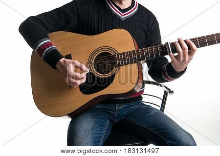 A Guitarist In Jeans And A Black Sweater Plays An Acoustic Guitar With A Slider Sitting On A Chair I