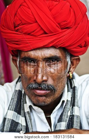 Jodhpur India - september 10 2010: Portret of Indian man in Rajastan Jodhpur in red turban gold earrings and moustache