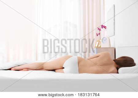 Young woman lying on orthopedic pillow against light background. Healthy posture concept