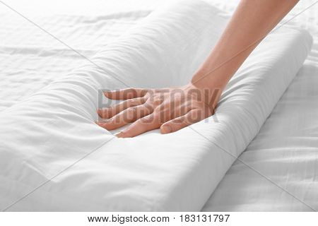 Female hand touching white orthopedic pillow. Healthy posture concept.