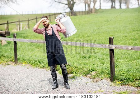 Full body portrait of a handsome milkman in apron with milk container outdoors on the rural scene background