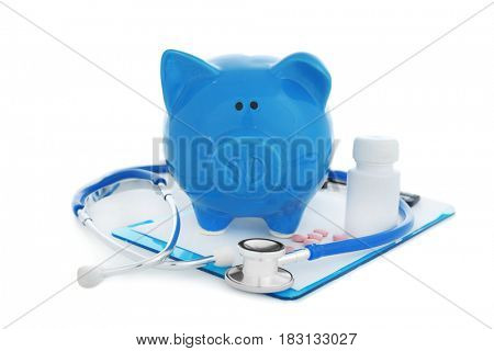 Ceramic piggy bank with stethoscope and pills on white background