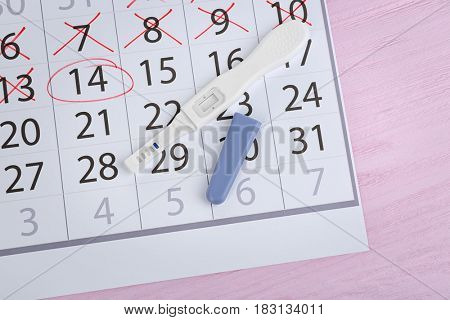 Calendar with pregnancy test on wooden background
