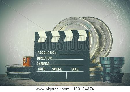 Clapperboard tin boxes with film and lens stand on a wooden table.Stylized photo