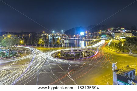 Dalat, Vietnam - March 27th, 2017: Roundabout intersections with lights Dalat night market, creating in streaks of color motorcycle stayed in the city for the evening mist Da Lat, Vietnam