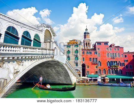 Famous Ponte Di Rialto With Traditional Gondola Under The Bridge In Venice, Italy