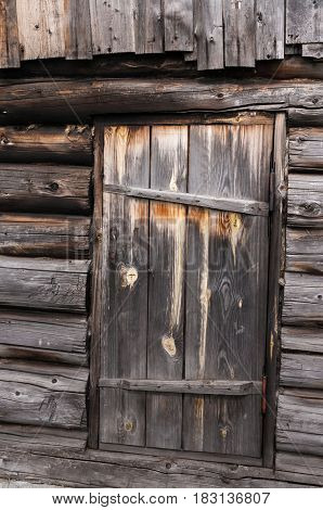 Old faded from time wooden door on log wall of house.