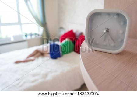 White Alarm Clock On Background Of Sleeping On The Bed Girl In The Early Morning.