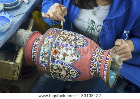 SHANGHAI China. April 20 2017: Close up of woman hand painting a Chinese vase in Shanghai China