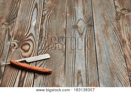 Vintage barber shop straight razor tool on old wooden background