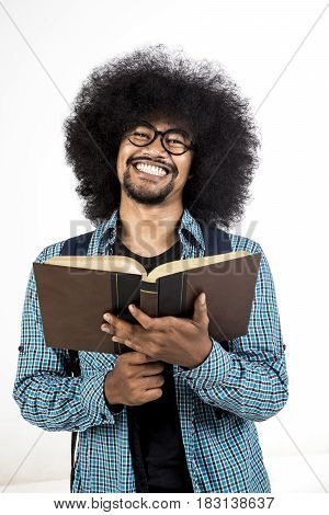 Young afro man smiling at the camera while holding his textbook isolated on white background
