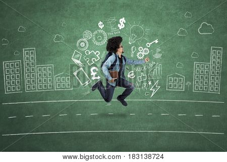 Young student running with doodle and scribble on chalkboard while holding a book