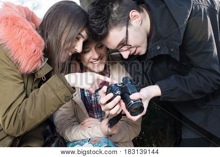 Young photographer and two smiling high school girils