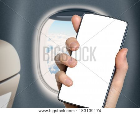 hand with blank mobile phone in front of airplane or jet window