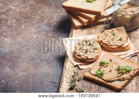 Fresh homemade chicken liver pate on bread over rustic background