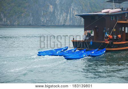 Halong Bay Vietnam - March 7 2017: travel boat with kayaks near Cat Ba island Halong Bay Vietnam