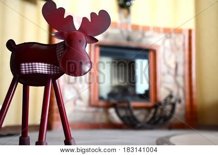 Statuette of a deer close-up against a fireplace
