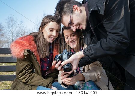 Young smiling photographer shows photos on display to the girls