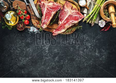 Raw dry aged t-bone steaks for grill with fresh herbs and vegetables