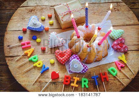 Birthday cake with burning candles, gift box and hearts on wooden table