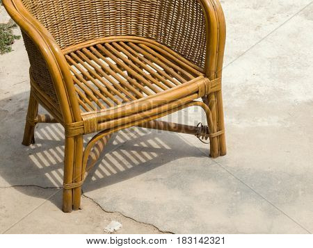 COLOR PHOTO OF RATTAN CHAIR ON CONCRETE GROUND