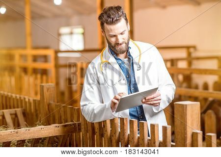 Handsome doctor in medical gown with digital tablet taking care about goats at the barn