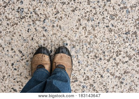 Men legs in dirty sport sneakers on old asphalt with raindrops, top view