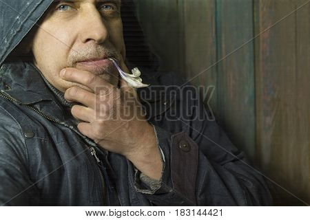 Romantic looking man holding a young daffodil in the mouth studio portrait