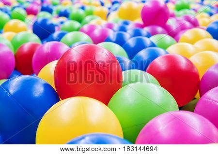 A large red ball among a multitude of plastic colored children balls