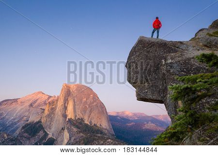 A fearless hiker is standing on an overhanging rock enjoying the view towards famous Half Dome at Glacier Point overlook in beautiful post sunset twilight Yosemite National Park California USA