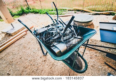 Wheelbarrow Full Of Roofing Metal Waste Material On Construction Site.