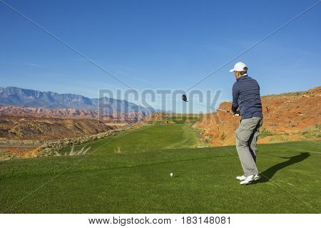 Rear view of a man playing golf on a Sunny day on a beautiful desert golf course in the Southwestern United states.