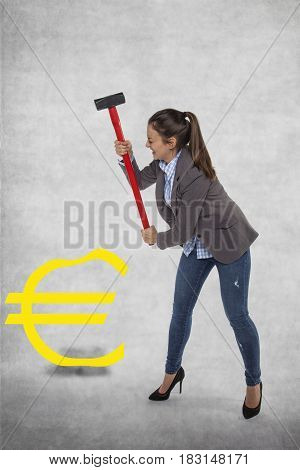 Business woman destroying the euro symbol, big hummer