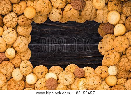 Cookies frame background. Sweet chocolate chips biscuits on brown rustic wood with copy space.