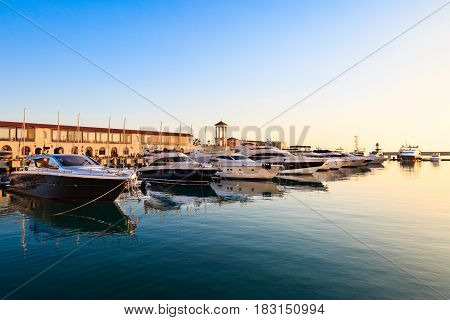 Luxury yachts and motor boats in sea port at sunset.