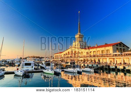 SOCHI, RUSSIA - MARCH 09 , 2017: Commercial Sea Port of luxury yachts, motor and sailing boats, seaport in Black sea at sunset. Reflection of Marine station in water.
