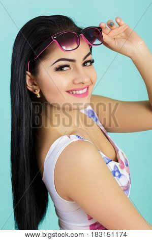 attractive young brunette woman in pink tank top on the blue background. smilling girl in sunglasses