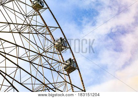 Ferris wheel on colorful sky background. Amusement park.