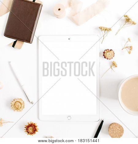 Blogger or freelancer workspace with tablet coffee mug notebook and accessories on white background. Flat lay top view minimalistic brown styled home office desk. Beauty blog concept.