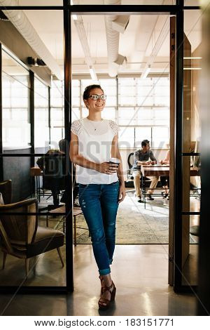 Full length portrait of smiling caucasian woman standing in office doorway with coffee and looking away. Female having coffee break at startup.