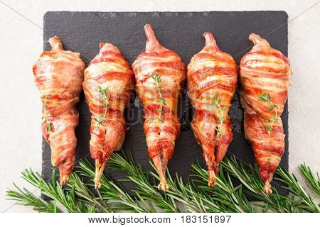 Baked Quail Wrapped In Bacon On A Slate Board With Spices