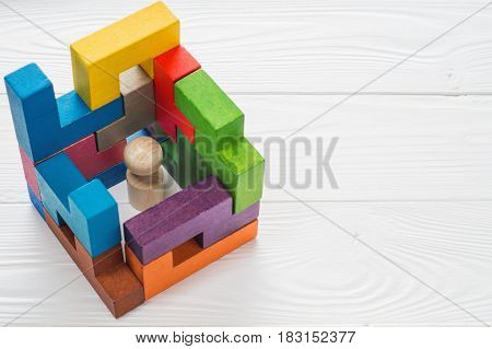 Business metaphor businessman in a trap on white wooden background with copy space. Businessman trapped inside a abstract room from colourful wooden blocks. The concept of problems in business.