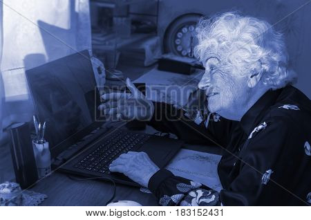 Happy merry grandmother learns to work at home on the computer and internet, blue tone