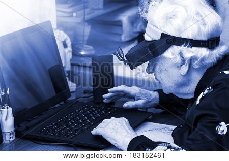 grandmother learns to work at home on the computer and internet In big special glasses virual reality, blue tone