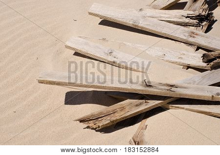 Broken beach defences lying in the sand