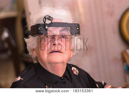 Grandmother in the big special glasses of the electronics engineer watchmaker